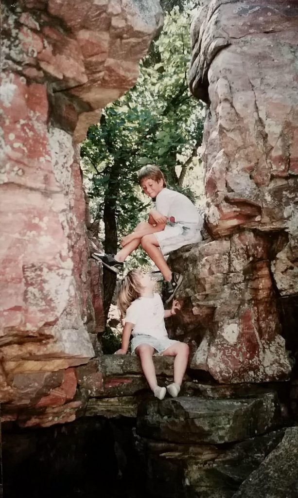 Aaron and his sister as children climbing rocks