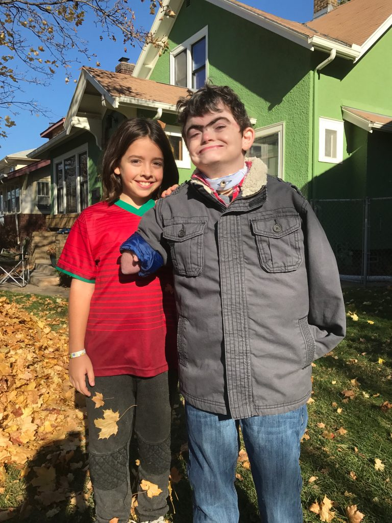 4th grader Lillian Guidry stands next to her older brother, Caleb Guidry, outside of a green house
