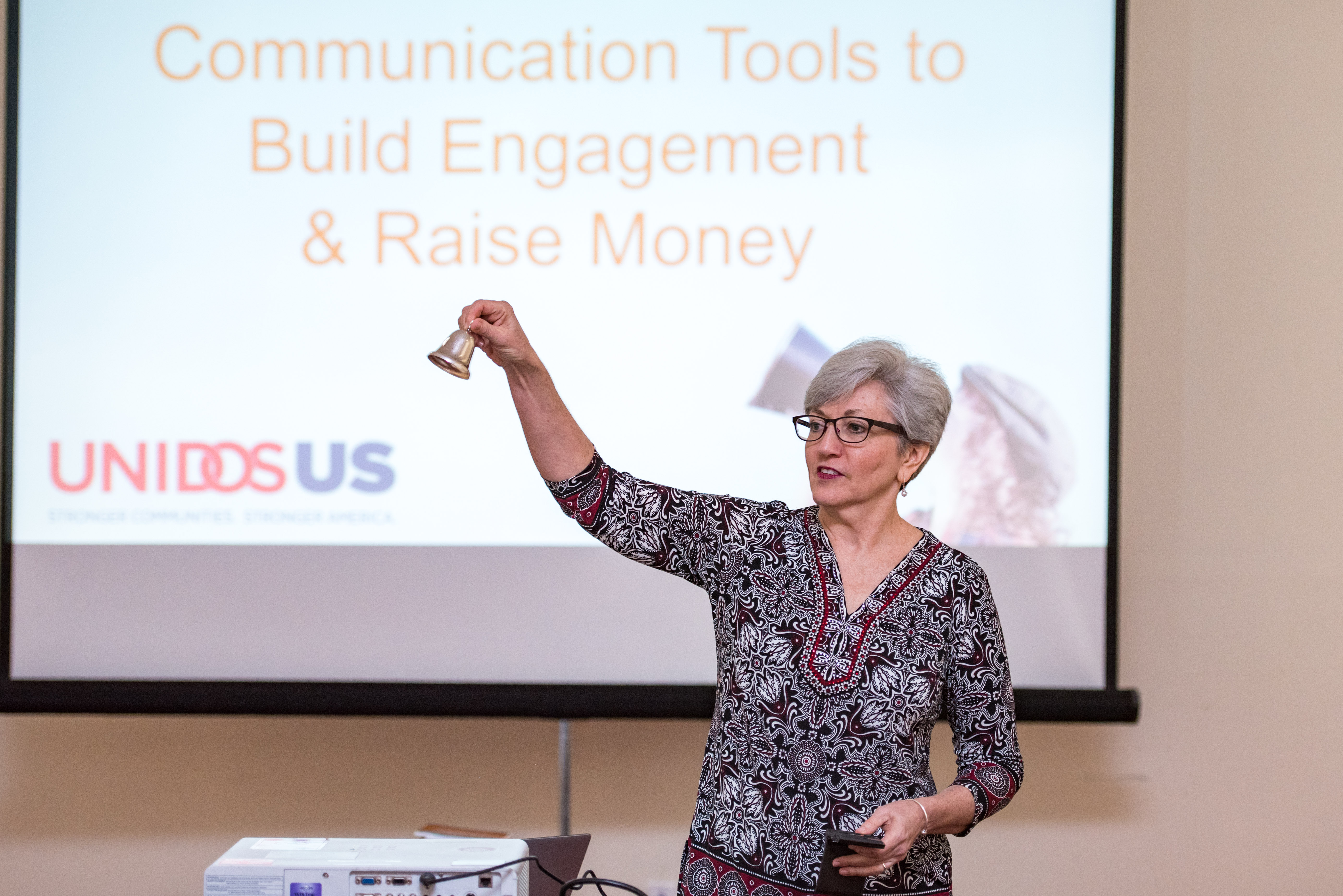 "Lori Jacobwith, of Ignited Fundraising, holding a bell in front of a slide reading ""Communication Tools to Build Engagement and Raise Money"""