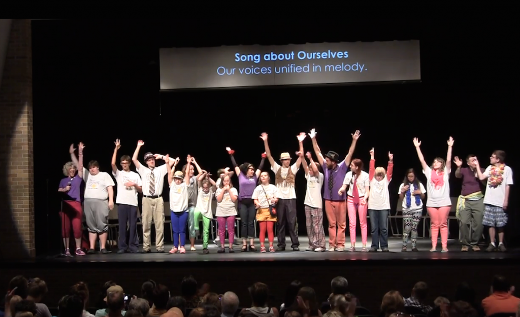 The cast of the 2014 Art of Me lines the front of the stage, raising their arms