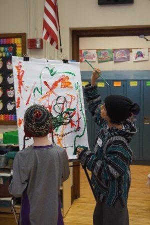 Students collaboratively painting in an Upstream Arts program