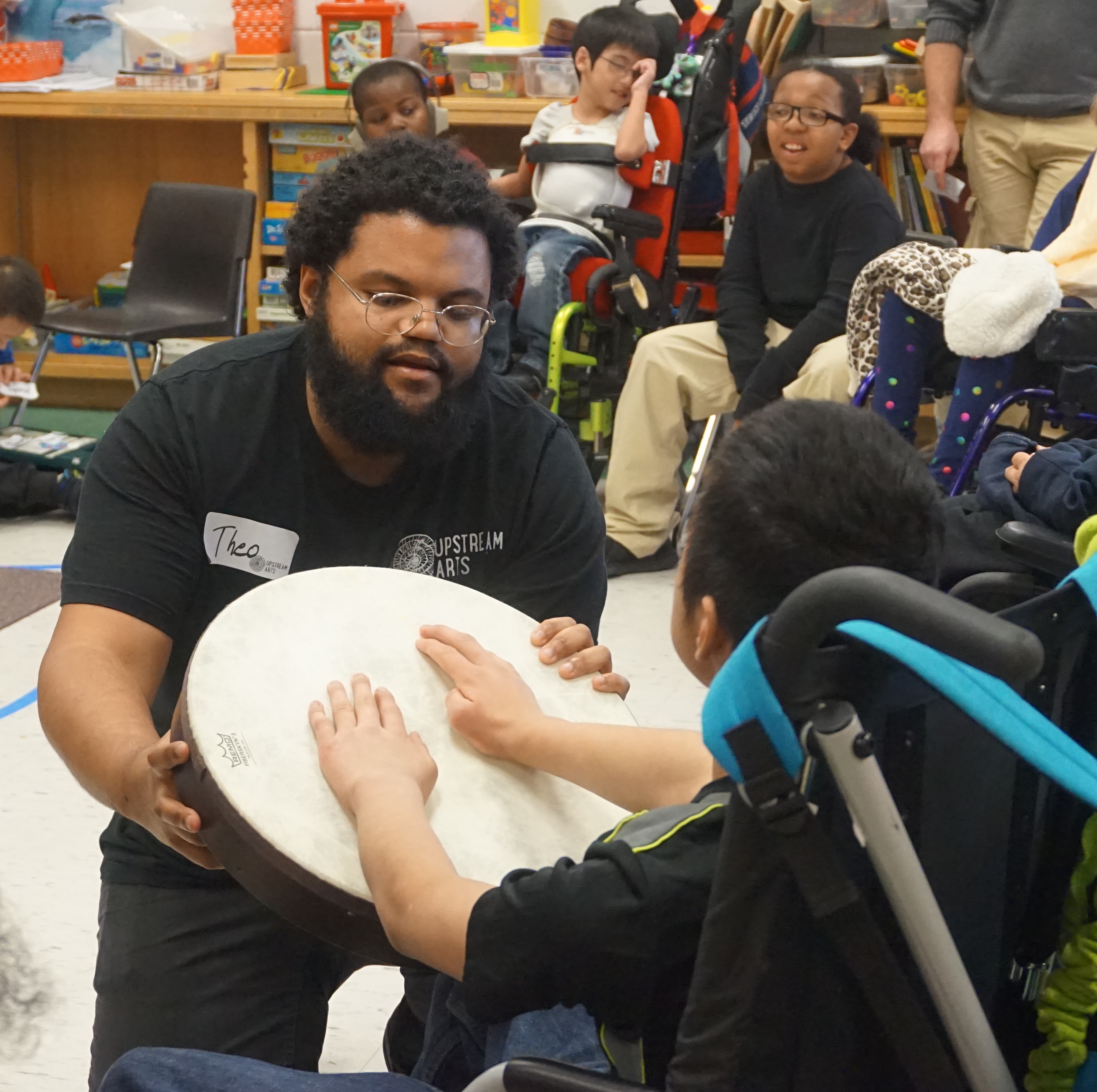 A Teaching Artist and Participant drumming.