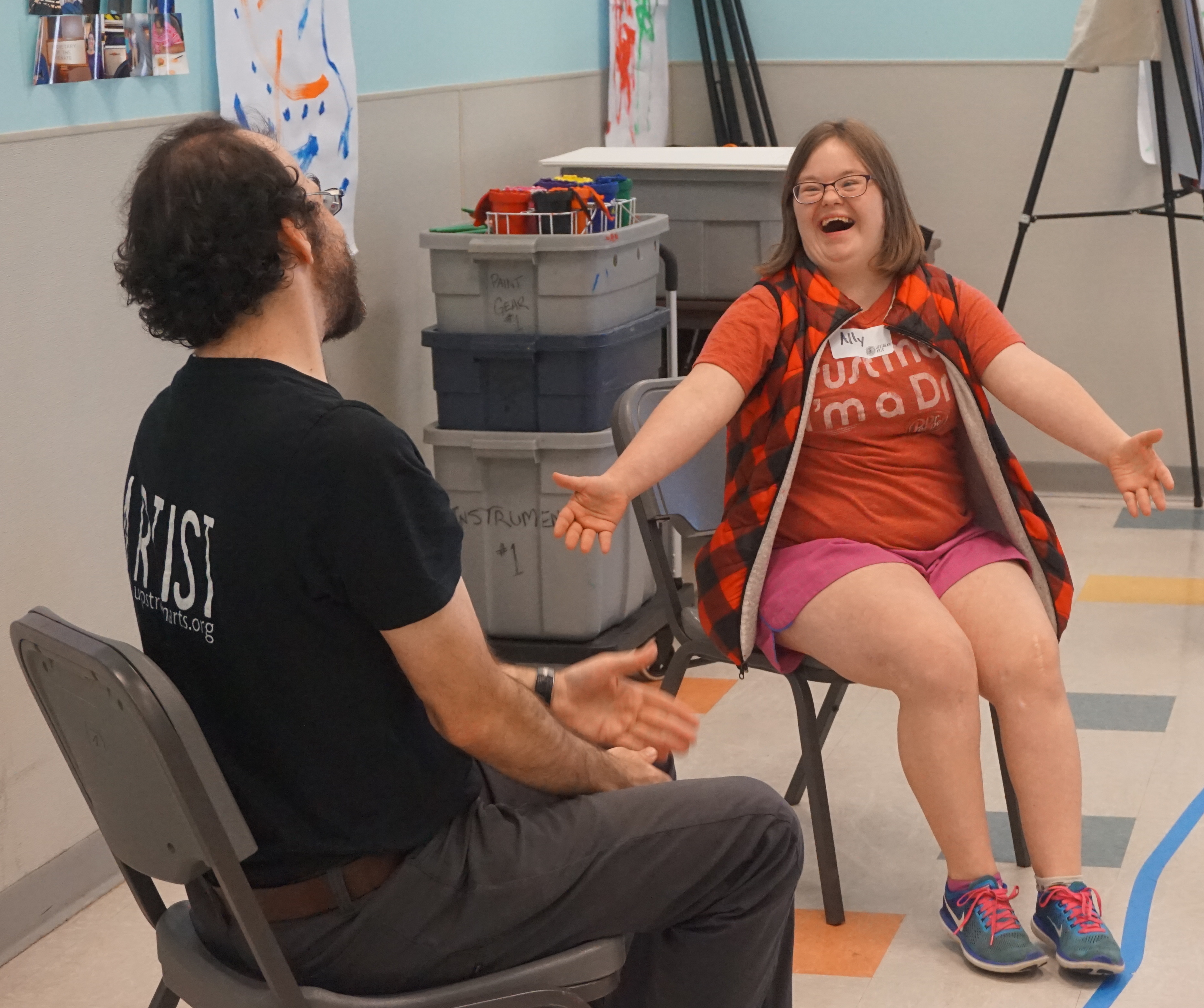 An Upstream Arts Teaching Artist and Participant sitting in chairs, practicing an acting scenario