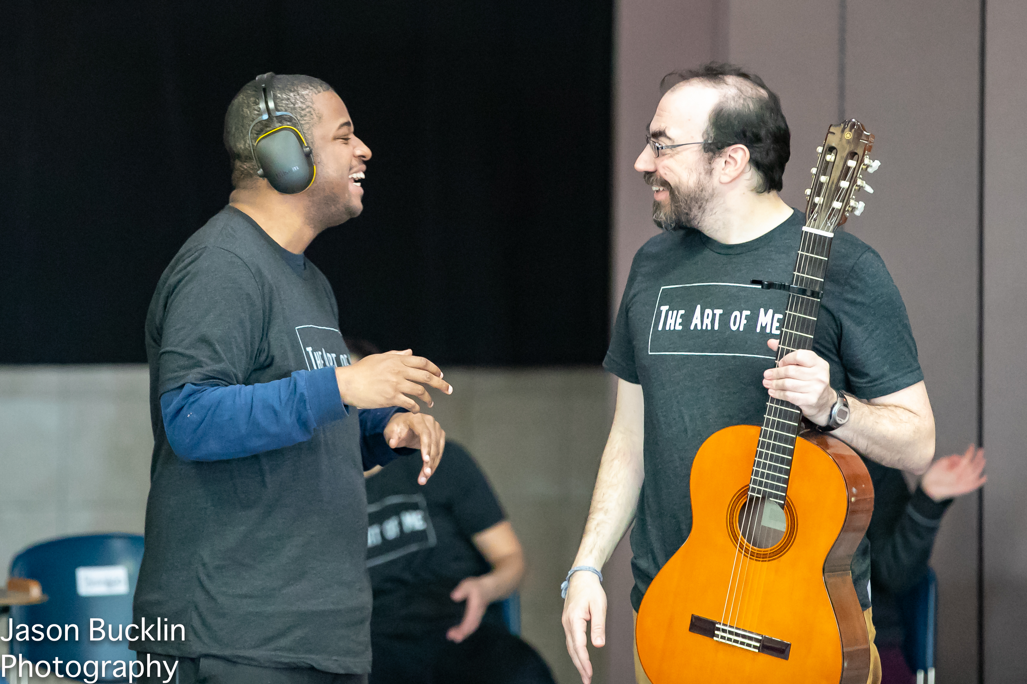 A singer and guitarist smile at each other.