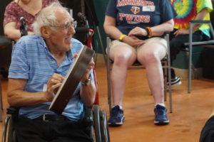 An elderly participant plays the drum