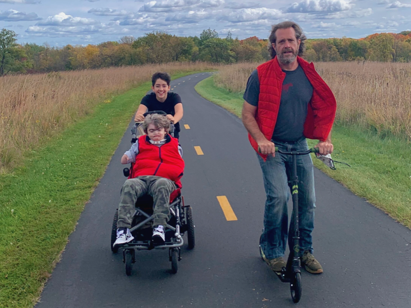 Matt Guidry, a slender white man with silver hair and beard, rides a scooter next to his children: Caleb, an adult with Cornelia de Lange syndrome who uses a chair, pushed by Lillian, a teenager with a mop of brown hair and a wide grin. They are on a park trail lined with tall prairie grasses.