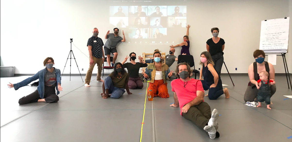 Group photo of our masked Staff and Teaching Artists in a dance studio, with online participants projected on the wall behind.